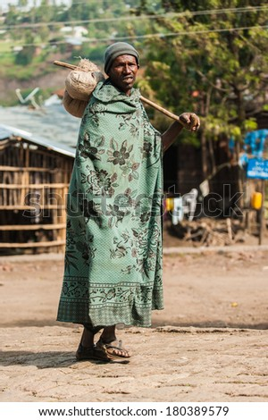 AKSUM, ETHIOPIA - SEPTEMBER 24, 2011: Unidentified Ethiopian man with his stuff on the stick on his shoulder. People in Ethiopia suffer of poverty due to the unstable situation