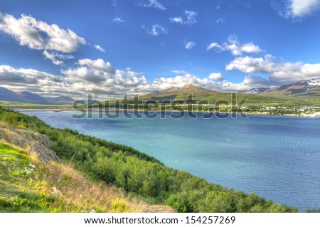 Akureyri viewed from the eastern shore of Eyjafjordur in Iceland - Eyjafjordur is the longest fjord in Iceland. It is located in the central north of the country. - stock photo
