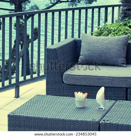 Al fresco cafe with rattan furniture on the terrace, Lake Geneva, Switzerland. Square toned image, instagram effect - stock photo