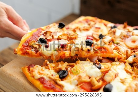 Al funghi pizza cut in sectors with one piece taken in hand selective focus horizontal - stock photo