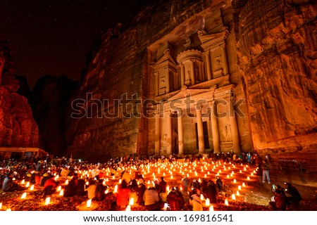 Al Khazneh in Petra, Jordan at night.  Al Khazneh was carved out of a sandstone rock face.  It has classical Greek-influenced architecture and is known as The Treasury. - stock photo