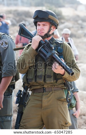 AL-WALAJA  - NOVEMBER 13: An Israeli soldier with a tear gas gun stands by during a protest against Israel's separation wall on Nov. 13, 2010 in Al-Walaja. - stock photo