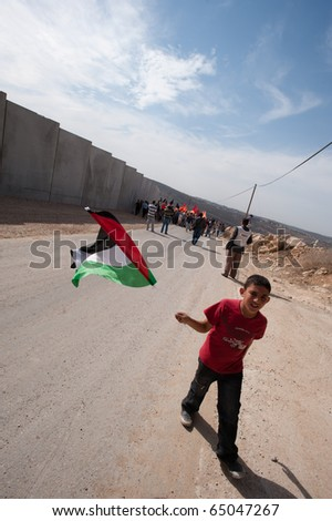 AL-WALAJA - NOVEMBER 13: An unidentified boy waves a Palestinian flag on Nov. 13, 2010 in a nonviolent protest against the Israeli separation barrier in Al-Walaja.