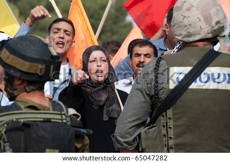 AL-WALAJA - NOVEMBER 13: An unidentified  Palestinian woman confronts Israeli soldiers in a protest against the Israeli separation wall on Nov. 13, 2010 in Al-Walaja, West Bank. - stock photo
