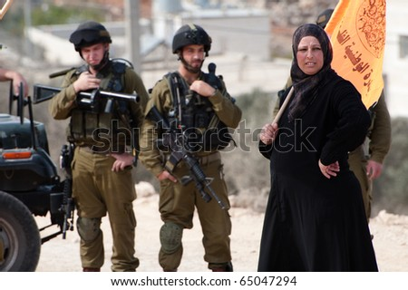 AL-WALAJA - NOVEMBER 13: An unidentified Palestinian woman confronts Israeli soldiers in a protest against the Israeli separation wall on Nov. 13, 2010 in Al-Walaja. - stock photo