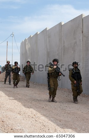 AL-WALAJA - NOVEMBER 13: Israeli soldiers stand in front of the Israeli separation barrier which threatens to encircle Al-Walaja on Nov. 13, 2010.