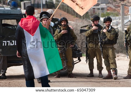 AL-WALAJA - NOVEMBER 13: Palestinian activists confront Israeli soldiers in a protest against the Israeli separation wall in Al-Walaja on Nov. 13, 2010. - stock photo