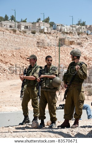 AL-WALAJA, OCCUPIED PALESTINIAN TERRITORIES - AUGUST 27:  Israeli soldiers stand in front of the Jewish settlement of Har Gilo during a protest in the West Bank town of Al-Walaja, Occupied Palestinian Territories on August 27, 2011. - stock photo