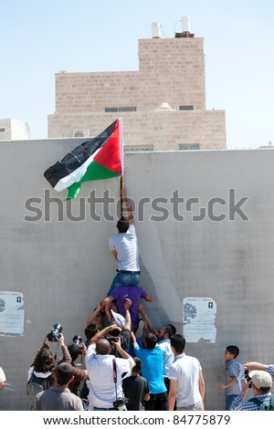 AL-WALAJA, OCCUPIED PALESTINIAN TERRITORIES - SEPTEMBER 16: Youth raise the Palestinian flag over the wall between the Israeli settlement Har Gilo and the West Bank town of Al-Walaja, Sept. 16, 2011. - stock photo