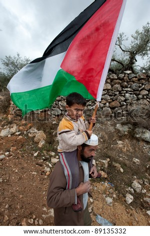 AL-WALAJA, PALESTINIAN TERRITORIES - NOVEMBER 18: An unidentified boy carries a Palestinian flag and rides on his father's shoulders protesting the Israeli separation wall in Al-Walaja, West Bank on Nov 18, 2011. - stock photo