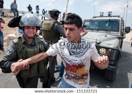 AL WALAJA, PALESTINIAN TERRITORY - MAY 10: Israeli soldiers arrest a Palestinian youth during a demonstration against the Israeli separation wall in the West Bank town of Al-Walaja, May 10, 2013. - stock photo