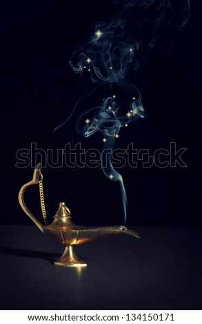 aladdin magic lamp on black with smoke - stock photo