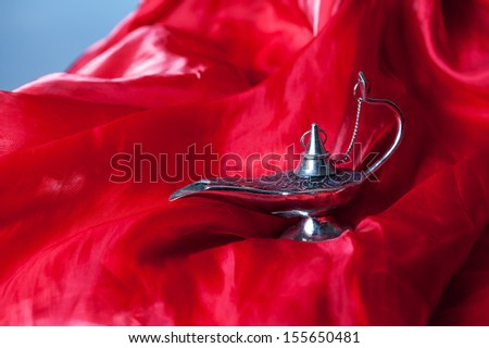 Aladdin's lamp on a red fabric - stock photo