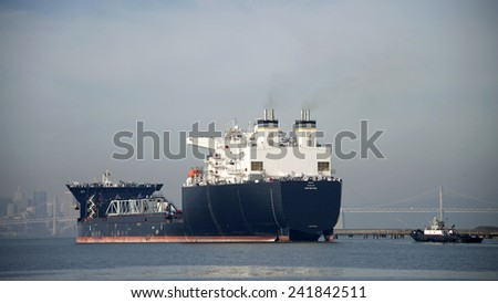 ALAMEDA, CA - JANUARY 05, 2014: Tugboat ASTORIA following U.S. U.S. Naval Ship MONTFORD POINT, a Mobile Landing Platform (MLP), away from the docks at Alameda Point through the San Francisco Bay. - stock photo