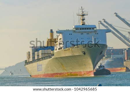 "Alameda, CA - March 9, 2015: Oakland Container Shipyard, San Francisco Bay the Matson container ship ""MANOA"" entering harbor and maneuvering into dock"