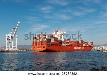 "Alameda, CA - March 9, 2015: Oakland Oakland Container Shipyard, San Francisco Bay, the Hamburg Sud ship ""Santa Barbara"" entering harbor, maneuvering into dock - stock photo"