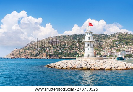Alanya lighthouse with fortress on the background - stock photo