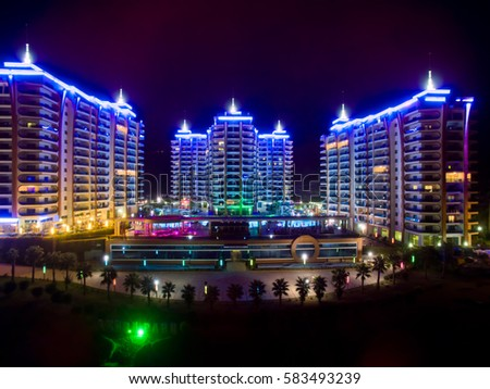 ALANYA, TURKEY - AUG 16, 2015: Three buildings of the residential complex Azura Park Residence with evening color light at night, aerial photo