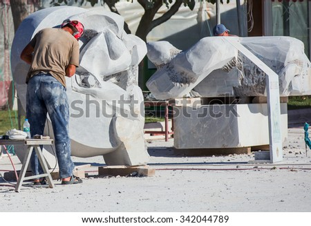 ALANYA, TURKEY - NOVEMBER 19, 2015: A carvers using a tool on a marble to carve a statue