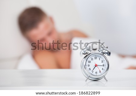Alarm clock about to ring in the morning showing a quarter past seven with a man sleeping in bed in the background  focus to the clock - stock photo