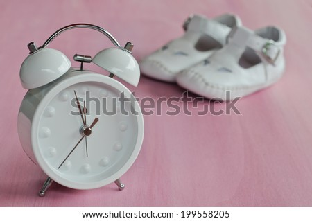 Alarm clock and baby shoes on pink background - stock photo