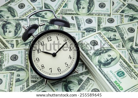 alarm clock and banknotes of one hundred dollars - stock photo