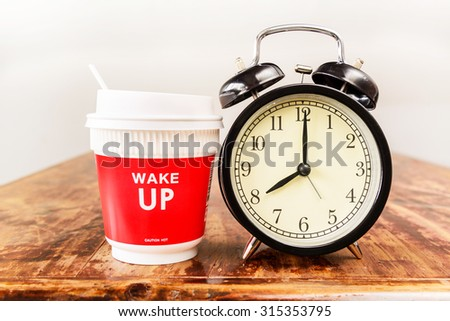 Alarm clock and coffee cup, Eight o'clock in the morning. - stock photo