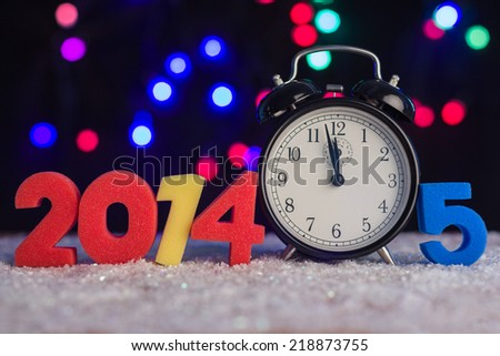 Alarm clock and figures in 2014 and 2015. - stock photo