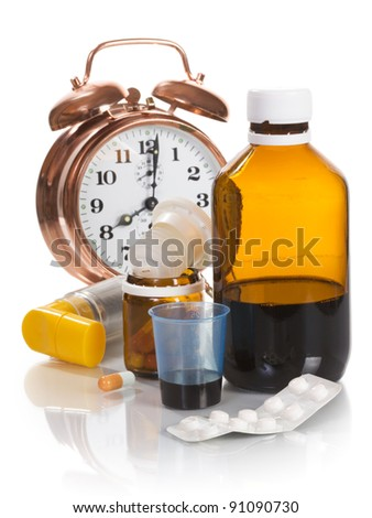 Alarm clock and medicine on white background - stock photo