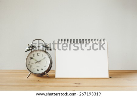 alarm clock and paper sign on wood table. Vintage tone - stock photo