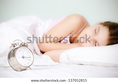 alarm clock and sleeping girl - stock photo