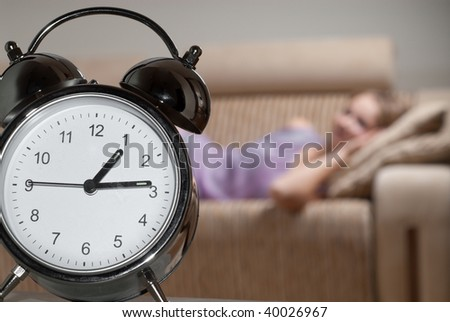 Alarm clock and sleeping girl on blurred background