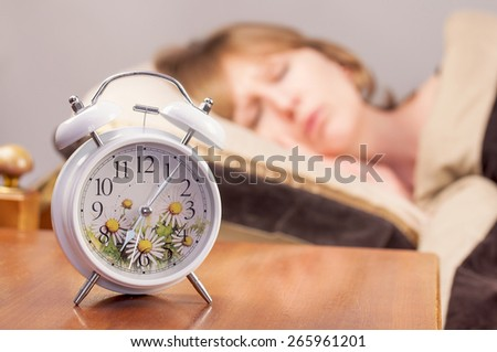 alarm clock and sleeping girl on the background - stock photo