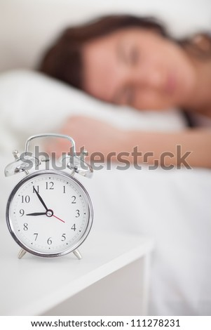 Alarm clock being placed on a bedside table in a bedroom - stock photo