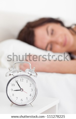 Alarm clock being placed on a nightstand in a bedroom - stock photo