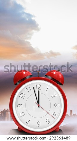 Alarm clock counting down to twelve against cityscape on the horizon - stock photo