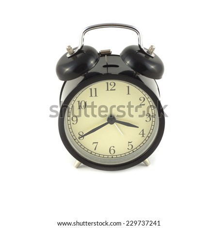 Alarm clock in black case shows about four o'clock. Photo isolated on white close up