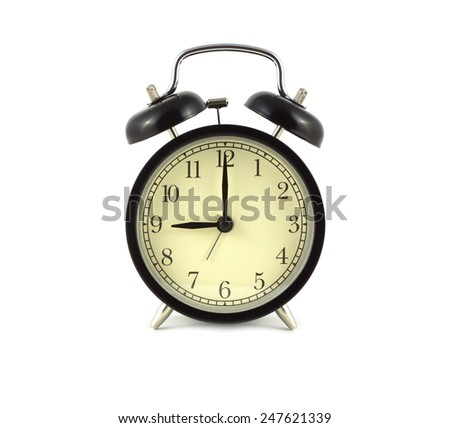 Alarm clock in black case shows 9 o'clock. Front view isolated on white close up