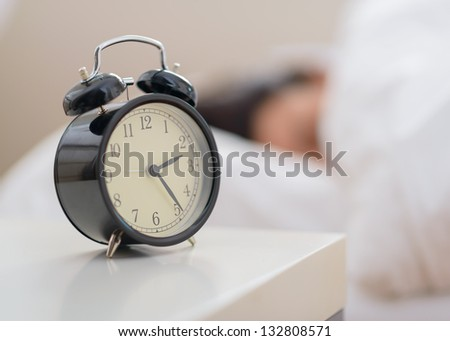 Alarm Clock In Front Of A Person Sleeping - stock photo