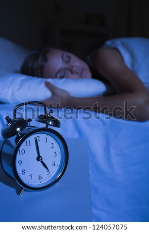 Alarm clock in front of a sleeping woman at night in the bedroom - stock photo