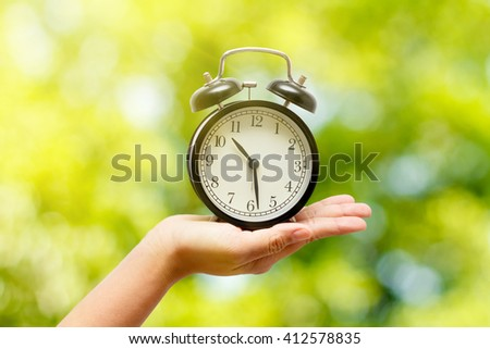 Alarm clock in hand on natural background. Summer Concep - stock photo