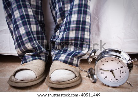 Alarm clock in the floor near an recently awake man - stock photo