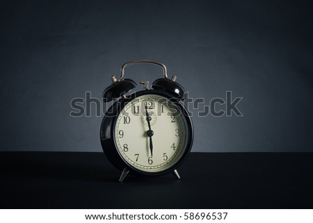 Alarm clock on a black background. - stock photo