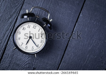 Alarm clock on a black wooden surface - stock photo