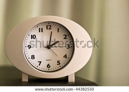 Alarm clock on a desk - stock photo