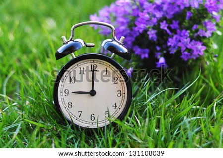 Alarm clock on a green grass - stock photo