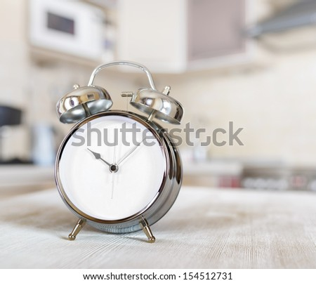 Alarm clock on a table in the kitchen. - stock photo