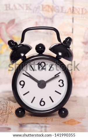 alarm clock on a ten pound note - stock photo