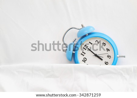 alarm clock on bed sheets - stock photo