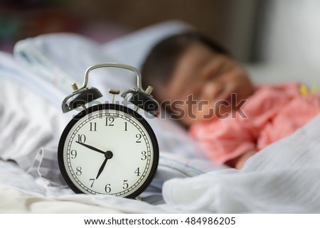 Alarm clock on bed with new born baby background
